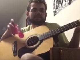 Casually Playing Wonderwall With a Pink Dildo Is One Way Of Making It In The Music Biz