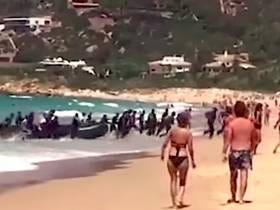 A Boat Full Of Migrants Came In With The Tide On A Beach In Spain